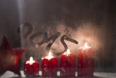 Bougies brûlantes d'avènement sur la fenêtre givrée avec le nouveau year 2015 Photo libre de droits
