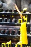 Bougies brûlantes dans une église de temple sur un fond noir Image libre de droits