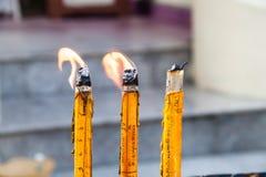 Bougies brûlantes dans une église de temple sur un fond noir Image stock