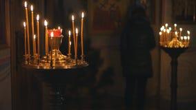 Bougies brûlantes dans une église orthodoxe Icônes et prière banque de vidéos