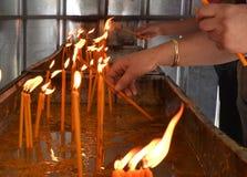 Bougies brûlantes de personnes dans une église d'otrhodox Images libres de droits