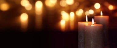 Bougies brûlantes la nuit avec le bokeh d'or Image libre de droits