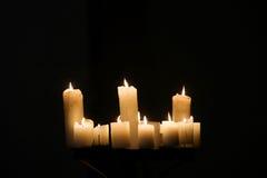 Bougies brûlantes sur le fond noir Photographie stock libre de droits