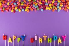 Bougies colorées de joyeux anniversaire pour le gâteau et les dragées à la gelée de sucre photo stock