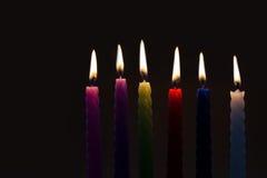 Bougies colorées sur le fond noir six morceaux chaque silhouette de bougie avec la vraie flamme Concept léger et d'obscurité Photos stock