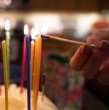 Bougies color?es d'anniversaire allum?es dans l'obscurit? image libre de droits