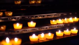 Bougies d'église dans des lustres transparents jaunes avec le fond foncé Image stock