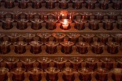 Bougies dans l'église Beaucoup de flammes de bougie rougeoyant dans l'obscurité photos libres de droits