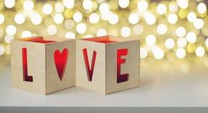 Bougies dans les boîtes en bois avec des lettres d'AMOUR Image libre de droits