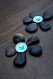 Bougies de bleu de turquoise avec les roches noires comme pétales formant la fleur Photos libres de droits