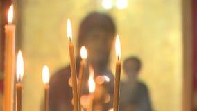 Bougies de cire dans la brûlure d'église banque de vidéos