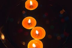 Bougies de cire dans la perspective d'une guirlande Photographie stock libre de droits