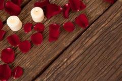 Bougies de cire entourées avec des pétales de rose Image libre de droits