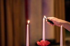 Bougies de foudre de main de femme sur le banquet avec l'arrangement rouge de table Photographie stock