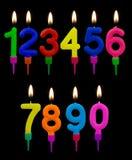 Bougies de gâteau d'anniversaire, nombres, avec des flammes au-dessus de noir Image stock