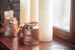 Bougies de Noël blanc et un pot en verre avec le filon-couche debout d'onwindow de ficelle rustique Images stock