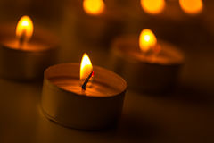 Bougies de Noël brûlant la nuit L'abstrait mire le fond Lumière d'or de flamme de bougie Images libres de droits