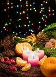 Bougies de Noël et ornements, mandarines nuts sur la toile à sac avec brûler le bokeh coloré Photo stock