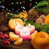 Bougies de Noël et ornements, mandarines nuts sur la toile à sac avec brûler le bokeh coloré Photographie stock