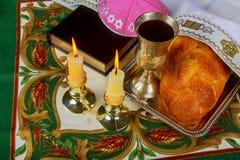 Bougies de Shabbat dans des chandeliers en verre avec le fond couvert brouillé de pain du sabbat Photographie stock