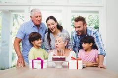 Bougies de soufflement d'anniversaire de grand-mère avec la famille Images stock