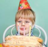 Bougies de soufflement d'anniversaire de jeune garçon Images stock