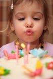 Bougies de soufflement d'anniversaire de petite fille photographie stock