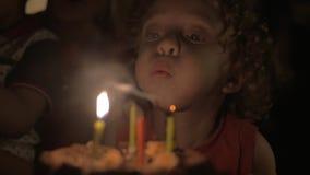 Bougies de soufflement d'enfant sur le gâteau d'anniversaire clips vidéos