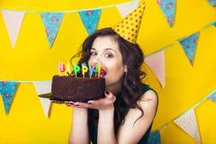 Bougies de soufflement de belle fille caucasienne sur elle gâteau Célébration et partie Photos libres de droits