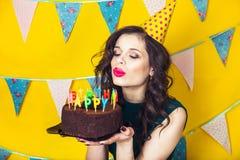 Bougies de soufflement de belle fille caucasienne sur elle gâteau Célébration et partie Image stock