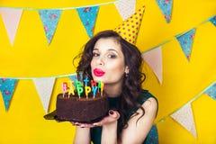 Bougies de soufflement de belle fille caucasienne sur elle gâteau Célébration et partie Photos stock