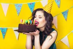 Bougies de soufflement de belle fille caucasienne sur elle gâteau Célébration et partie Images stock