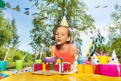 Bougies de soufflement de fille adorable sur le gâteau d'anniversaire Photographie stock libre de droits
