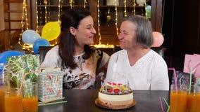 Bougies de soufflement de fille et de mère supérieure sur la partie de gâteau d'anniversaire ou de jour de mères