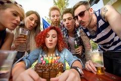 Bougies de soufflement sur le gâteau d'anniversaire de chocolat Image stock