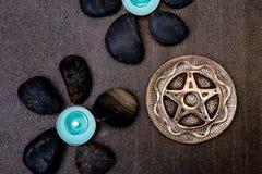 Bougies de turquoise avec les roches noires et pentagone étoilé argenté sur le gris Images libres de droits