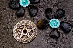 Bougies de turquoise avec les roches noires et pentagone étoilé argenté sur le gris Photo stock