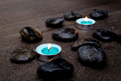 Bougies de turquoise avec les roches noires sur le fond gris d'ardoise avec Images stock