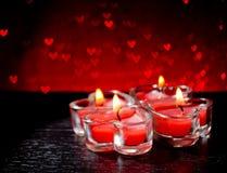 Bougies en forme de coeur brûlantes de rouge sur le bokeh rouge de coeurs Image stock