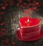 Bougies en forme de coeur brûlantes de rouge sur le fond en bois. Image libre de droits
