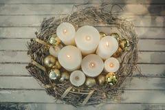 Bougies et boule de babiole dans le panier de nid sur la planche en bois Photographie stock
