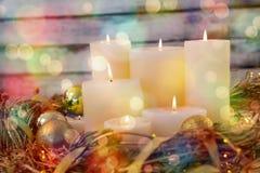 Bougies et boule de babiole dans le panier de nid sur la planche en bois Photos stock