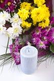 Bougies et fleurs d'isolement sur le blanc Images stock