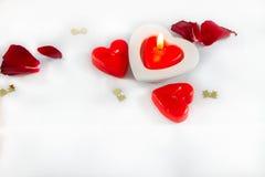 Bougies et pétales de rose en forme de coeur de jour de valentines sur le CCB blanc Image stock