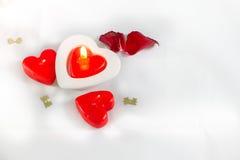 Bougies et pétales de rose en forme de coeur de jour de valentines sur le fond blanc Photo stock