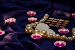 Bougies flairées, une palette des ombres, un coeur et belles perles sur une couverture image stock