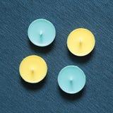 Bougies jaunes et bleues sur le fond de tissu de marine Photo libre de droits