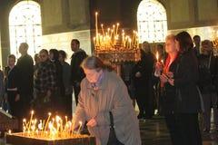 Bougies légères de personnes pendant la prière de fête dans l'église Images libres de droits