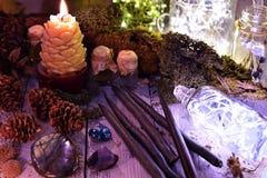 Bougies noires, cônes, éléments de nature et bouteille brillante sur la table photo stock