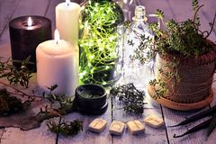 Bougies noires et blanches, usine succulente, vieilles bouteilles et runes sur la vieille table en bois image libre de droits
